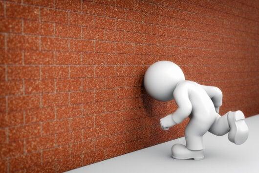 Mannetje ramt zijn hoofd tegen de muur, als voorbeeld van zelfkastijding