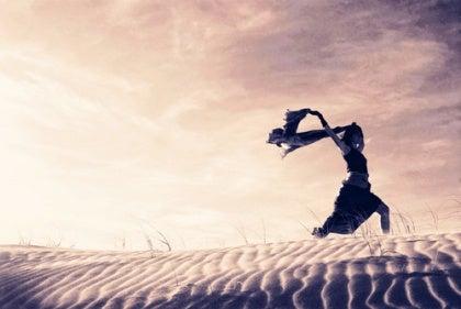 Vrouw is vrij en rent door het zand