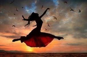 Vrouw maakt een sprong door de lucht en straalt kracht uit