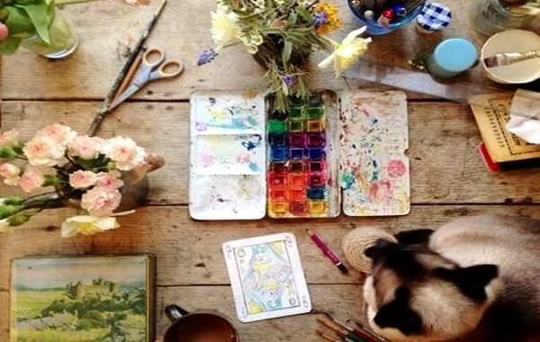 Een tafel vol verf en kwasten als voorbeeld van creativiteit