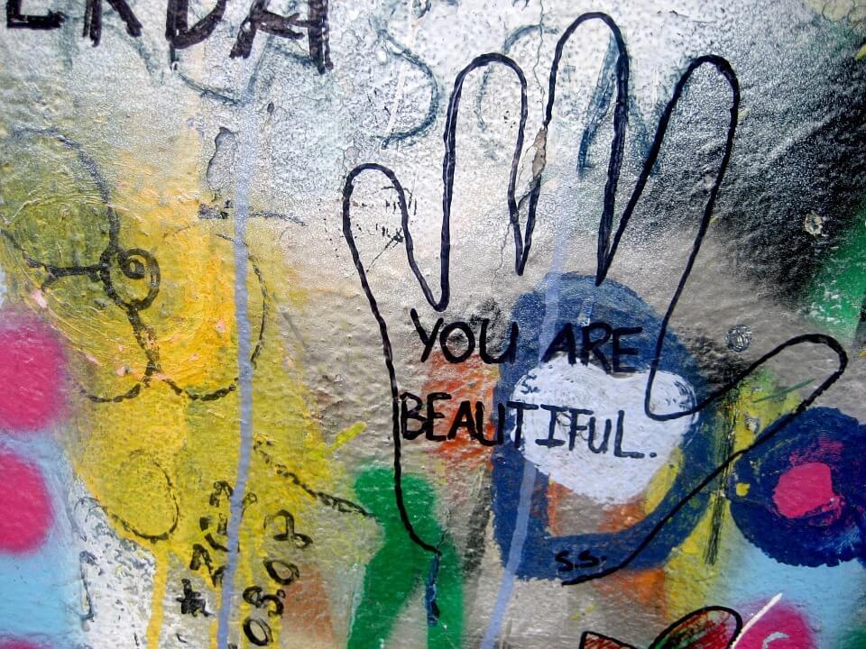 Muurschildering Van Bloemen En Een Hand Waar You Are Beautiful In Staat Geschreven