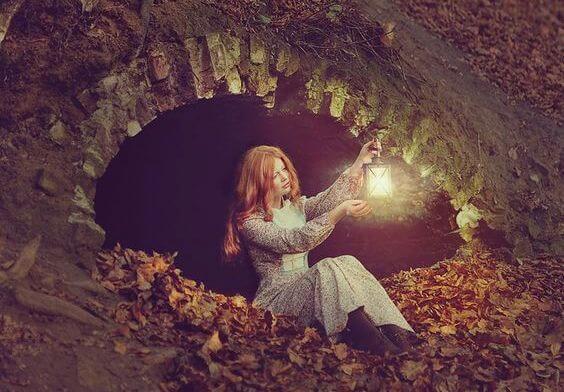Meisje Dat In Een Grot Zit Met Een Lantaarn In Haar Hand