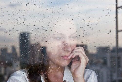 Vrouw Kijkt Uit Raam Op Regenachtige Dag En Kampt Met Nostalgie