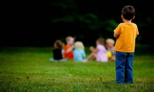 Jongetje Dat Alleen Staat Te Kijken Naar Een Groep Kinderen Verderop Als Voorbeeld Van Hoe Kinderen Die Lijden Aan Het Syndroom Van Asperger Zijn