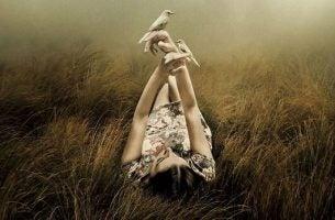 Meisje Dat In Het Gras Ligt Met Twee Vogeltjes Op Haar Handen Dat Haar Giftige Vrienden Gedag Heeft Gezegd