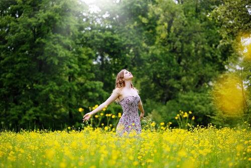 Vrouw Die In Een Grasveld Staat En Positieve Energie Uitstraalt Als Voorbeeld Van Hoe De Energie Van Anderen Ons Kan Beïnvloeden