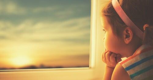 Meisje Dat Uit Haar Raam Kijkt Naar Een Zonsondergang