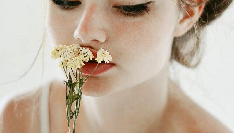 Meisje Dat Witte Bloemetjes Tegen Haar Mond Drukt