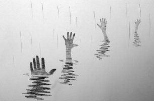 Handen die boven water uit proberen te steken als symbool voor het overwinnen van emotionele afhankelijkheid