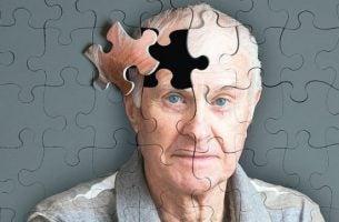 Puzzel van een man waarbij er een puzzelstukje uit zijn hoofd ontbreekt als symbool voor het verlies van het geheugen wat een van de waarschuwingstekens van Alzheimer is