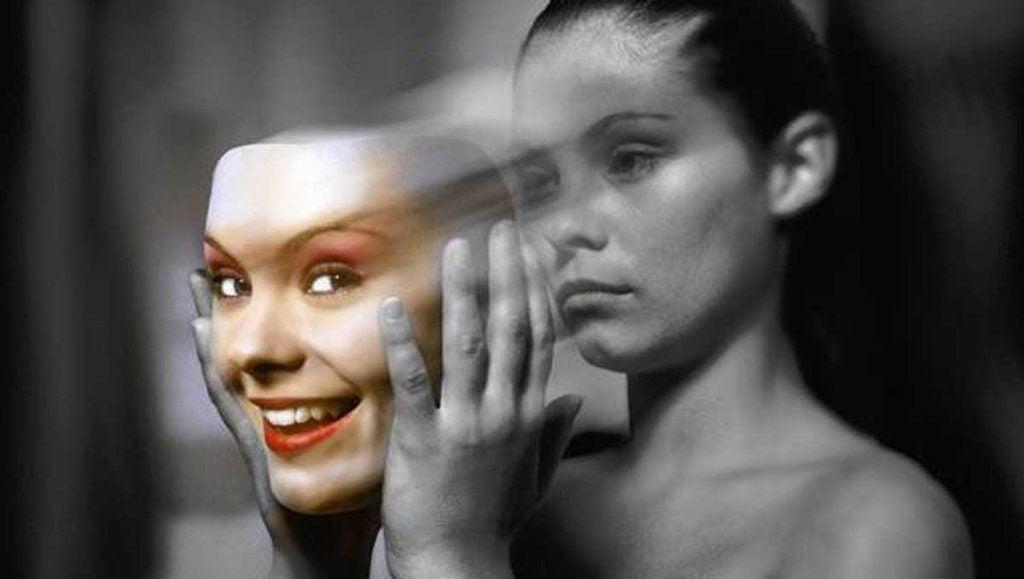 Meisje in zwart wit dat heel droevig kijkt en een vrolijk en kleurrijk masker van zichzelf van haar gezicht trekt als symbool voor bipolaire stoornis