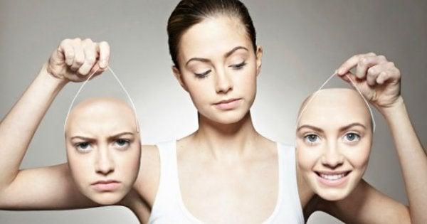 Meisje dat twee gezichten vasthoudt waarvan er een droevig kijkt en de ander vrolijk als voorbeeld van bipolaire stoornis