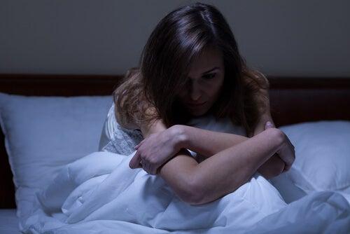 Vrouw die rechtop in bed zit en bang voor zich uit kijkt
