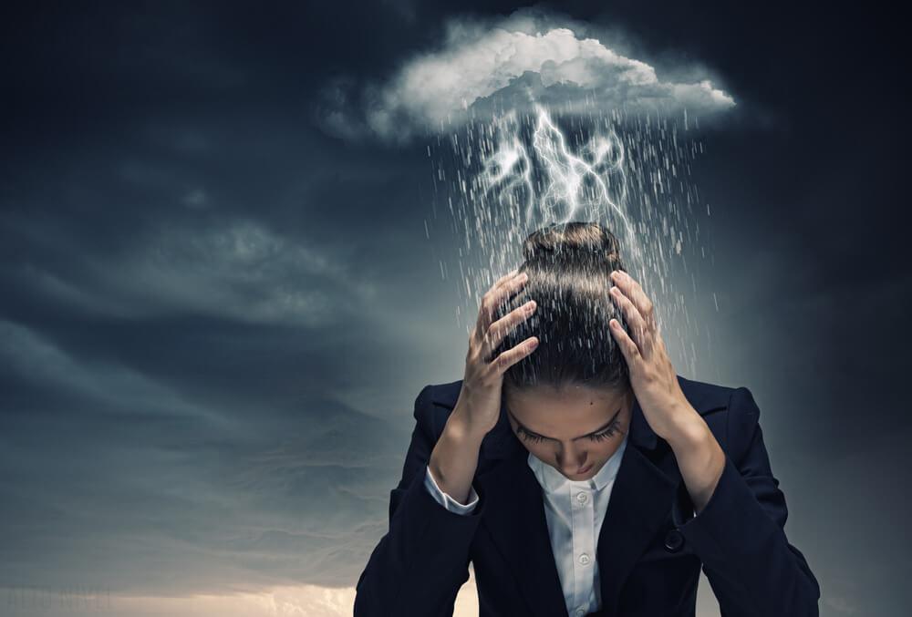 Vrouw die met haar hoofd omlaag gebogen staat omdat het vlak boven haar hoofd een stormwolk hangt als symbool voor bipolaire stoornis