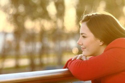 Meisje dat vrolijk voor zicht uitkijkt omdat ze haar negatieve gedachten heeft overwonnen