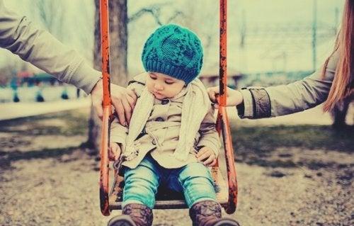 Een kindje dat op de schommel geduwd wordt door zijn gescheiden ouders