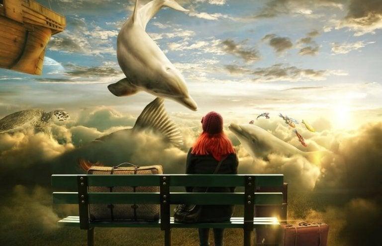 Meisje dat op een bankje zit en voor haar in de lucht zweven allemaal zeedieren is dit toeval of lotsbestemming?