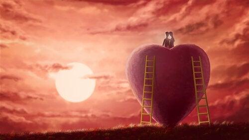 Twee zielen die op een groot hart geklommen zijn om naar de ondergaande zon te kijken als voorbeeld van ware intimiteit