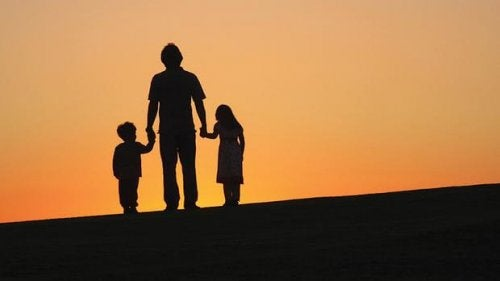 Een vader die met zijn twee kinderen wandelt