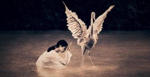 Een meisje dat knielt voor een vogel