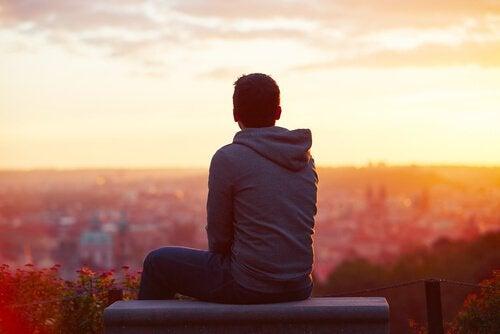 Jongen die vanaf een hoogte uitkijkt over zijn stad en nadenkt