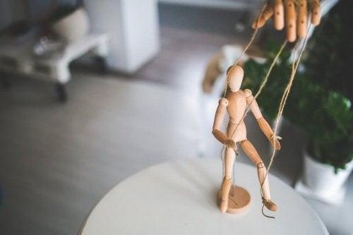 Een houten poppetje dat met touwtjes bespeeld kan worden