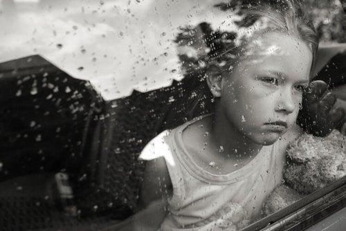 Een meisje dat bedroefd uit het raam kijkt