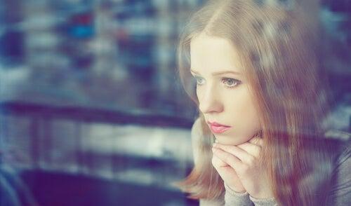 Meisje dat in gedachte voor zich uit zit te staren omdat ze met een probleem zit en dus veel zou hebben aan probleemoplossende therapie