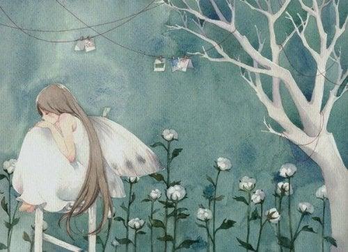 Meisje met vleugels dat teleurgesteld op een hekje tussen de bloemen zit, maar teleurstelling is behulpzaam in sommige gevallen