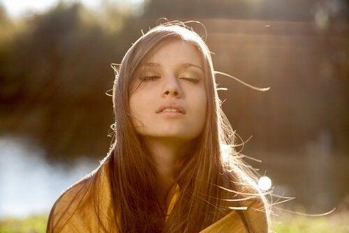 Meisje dat met ogen dicht geniet van de zon