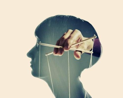 Het hoofd van een vrouw waar voor een hand die een marionet vasthoudt te zien is omdat deze vrouw het slachtoffer is van emotionele manipulatie