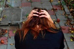 Meisje dat in de tuin zit met haar hoofd voorover gebogen omdat ze last heeft van obsessieve-compulsieve stoornis