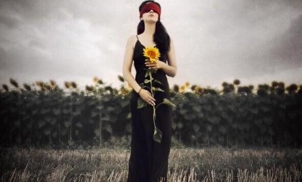 Een geblinddoekte vrouw die voor een veld met zonnebloemen staat en zelf ook een zonnebloem vasthoudt