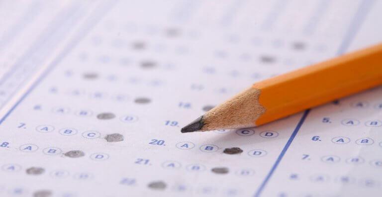 Potlood op een velletje papier waar antwoorden op staan