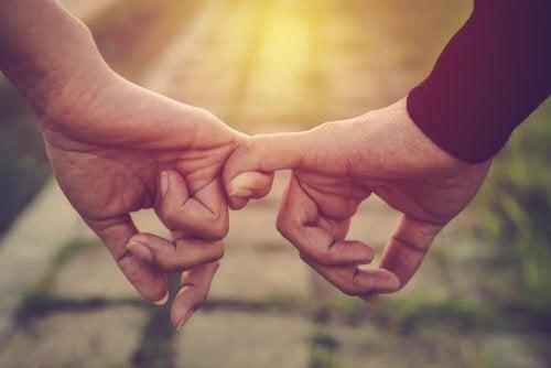 Twee mensen die elkaars pink vasthouden en elkaars onvolmaaktheden aanvaarden