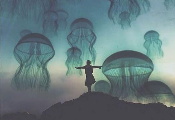 Vrouw die met gespreide armen op een heuvel staat en in de lucht zweven allemaal gigantische kwallen als symbool voor de giftige gewoonten die ons ongelukkig maken