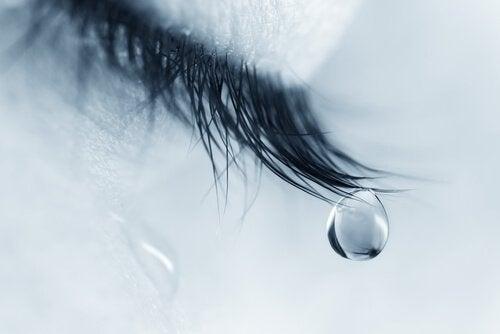 Traan die hangt aan die wimper van een vrouw die door het rouwproces gaat