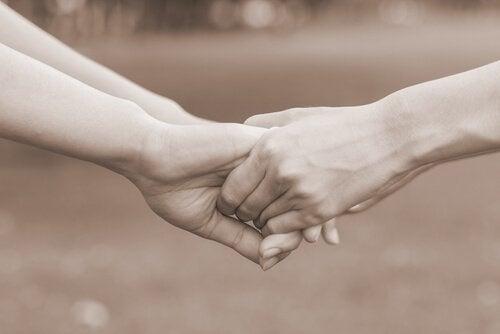 Twee paar handen die elkaar vasthouden