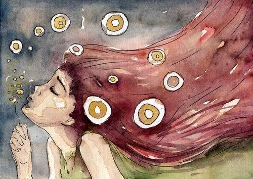 Een meisje met rood haar dat een paardenbloem wegblaast