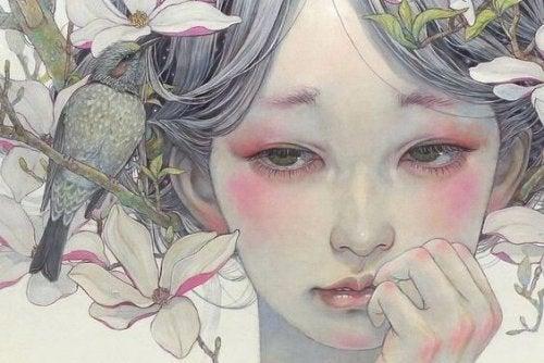 Meisje met bloemen in haar haar dat zeer droevig kijkt omdat ze last heeft van emotionele afhankelijkheid