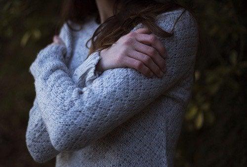 Vrouw die zichzelf omhelst want jezelf vergiffenis schenken is soms lastig