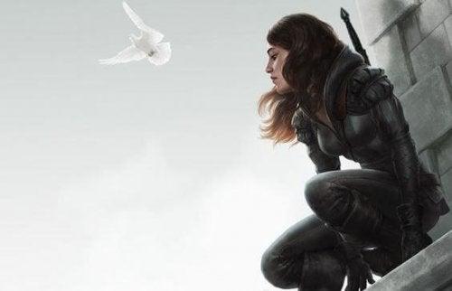 Meisje dat op de top van een gebouw zit en naast haar vliegt een witte duif