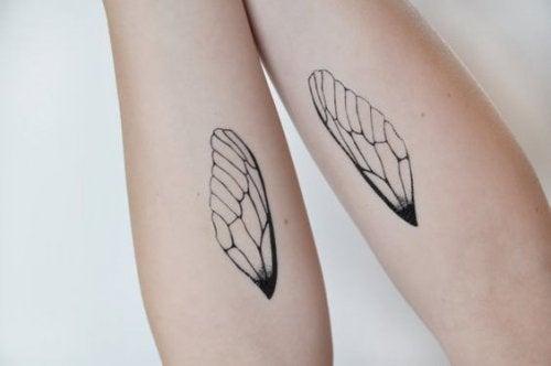 Meisje met op iedere arm een tattoo van een vleugeltje want de tijd vliegt, maar zij ook