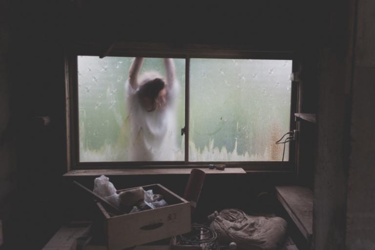 Vrouw die tegen een raam aan hangt omdat ze last heeft van dysthymie