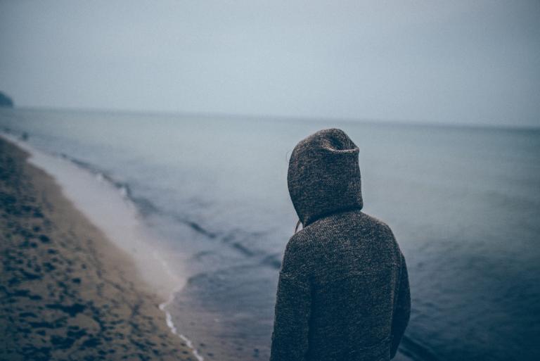 Jongen die alleen over het strand loopt, maar heeft hij last van depressie of dysthymie