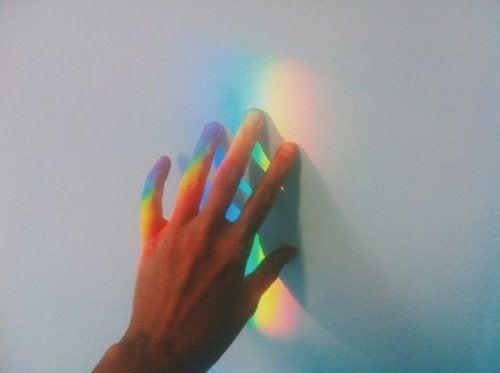 Hand raakt regenboog aan als voorbeeld voor de gave van hooggevoelige mensen.