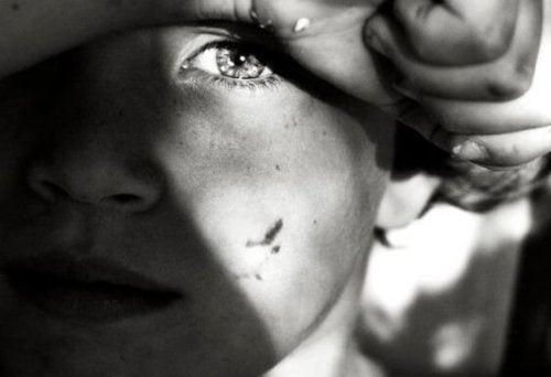 Zwart-witte afbeelding van een kind dat slachtoffer is van zijn emotioneel onvolwassen ouders