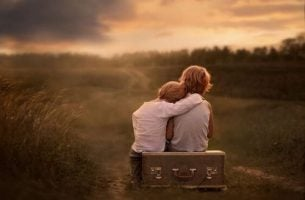 Twee jongetjes die op een koffer zitten bij zonsondergang en slachtoffer zijn van hun emotioneel onvolwassen ouders