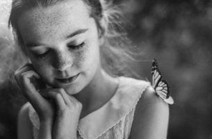 Klein meisje met vlinder op haar schouder denkt na over het geheim van geluk