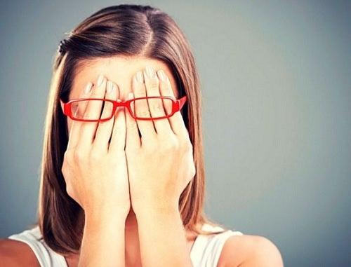 Meisje dat onder haar bril haar handen voor haar ogen houdt om zich te beschermen tegen mensen die geen goede bedoelingen hebben
